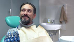 Smiling man in dental chair. stock video