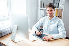 Smiling man designer working and using graphic tablet in office. Portrait of smiling young man designer working and using graphic tablet in office stock photography