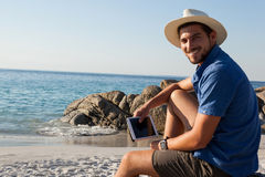 Smiling man with digital tablet sitting on beach Stock Photography
