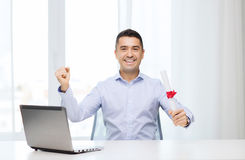 Smiling man with diploma and laptop at office Stock Photography
