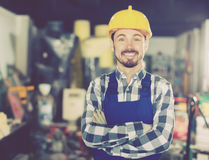 Smiling man displaying his workplace and tools. Young smiling man displaying his workplace and tools at workshop Royalty Free Stock Photos