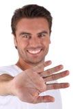 Smiling man displaying palm Stock Images