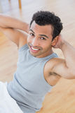 Smiling man doing abdominal crunches in the living room Royalty Free Stock Photos