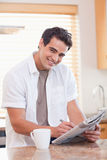 Smiling man doing crossword puzzle in the kitchen Stock Images