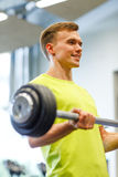Smiling man doing exercise with barbell in gym Royalty Free Stock Photography