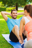 Smiling man doing exercises on mat outdoors Stock Photo
