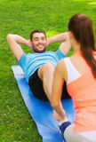 Smiling man doing exercises on mat outdoors Royalty Free Stock Photo