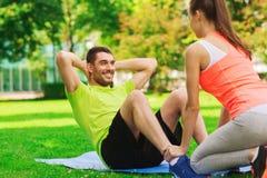 Smiling man doing exercises on mat outdoors Stock Photos