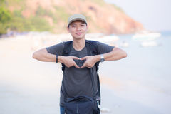 Smiling man doing heart shape with his hands the beach. Stock Photos
