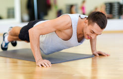 Smiling man doing push-ups in the gym Stock Photography