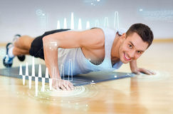 Smiling man doing push-ups in the gym. Fitness, sport, training, gym and lifestyle concept - smiling man doing push-ups in the gym Stock Photo