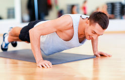 Smiling man doing push-ups in the gym Royalty Free Stock Image