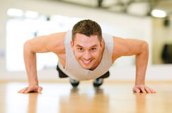Smiling man doing push-ups in the gym Stock Images