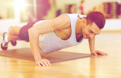 Smiling man doing push-ups in the gym Stock Image