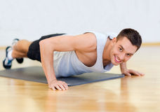 Smiling man doing push-ups in the gym. Fitness, sport, training, gym and lifestyle concept - smiling man doing push-ups in the gym or at home stock photo