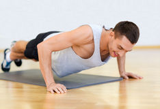 Smiling man doing push-ups in the gym Royalty Free Stock Images
