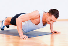 Smiling man doing push-ups in the gym Stock Photos