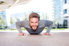 Smiling man doing push ups outdoors in the city Royalty Free Stock Image