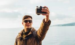 Smiling man doing self-portrait on coastline Stock Image