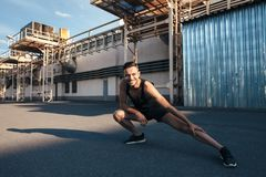Smiling man doing warm up and stretching outdoor on in industrial city background. Fitness, training, healthy lifestyle stock photography