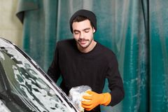 A smiling man washes a mirror of a car stock photo