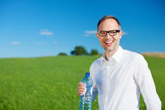Smiling man drinking bottled water Stock Photo
