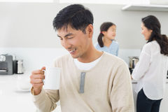 Smiling man drinking coffee with family in background Royalty Free Stock Images