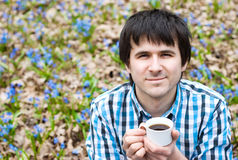 Smiling man drinking coffee in forest. Smiling man drinking coffee on nature. Enjoyment Royalty Free Stock Photo