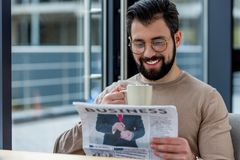 smiling man drinking coffee with marshmallow and reading royalty free stock photo