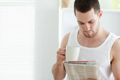 Smiling man drinking coffee while reading the news Stock Images