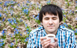 Smiling man drinking coffee in  wood. Smiling man drinking coffee on nature. Enjoyment Royalty Free Stock Photography