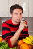 Smiling man drinking fresh orange juice Stock Photo