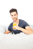 Smiling man is drinking orange juice in the bed. Photo of smiling man in the bed with orange juice Royalty Free Stock Photo