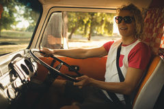 Smiling man driving camper va. Smiling man wearing sunglasses while driving camper van Stock Photography
