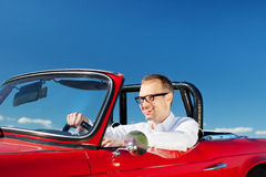 Smiling man driving a red cabriolet Stock Image