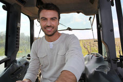 Smiling man driving tractor Stock Photo