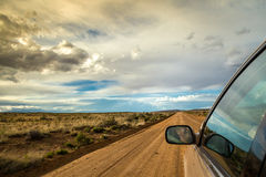 Smiling man driving through wilderness on dirt road Stock Image