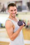 Smiling man with dumbbell in gym Royalty Free Stock Photography