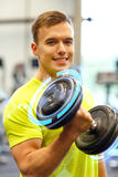 Smiling man with dumbbell in gym Stock Photo