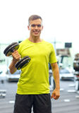 Smiling man with dumbbell in gym Royalty Free Stock Image