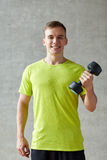 Smiling man with dumbbell in gym Royalty Free Stock Images