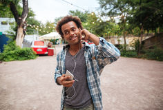 Smiling man in earphones listening to music from cell phone Stock Photography