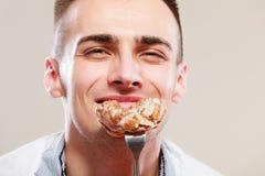 Smiling man eating cake. Stock Images