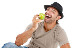 Smiling man eating an green apple Stock Images