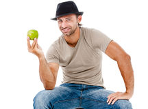 Smiling man eating an green apple Stock Photography