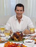 Smiling man eating turkey in Christmas dinner stock images