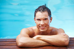 Smiling man at edge of pool Stock Photo