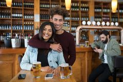 Smiling man embracing woman in bar Royalty Free Stock Photography