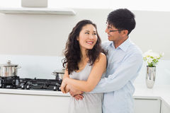 Smiling man embracing woman from behind in kitchen Stock Images