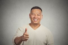Smiling man employee giving thumbs up sign gesture. Closeup portrait happy handsome young smiling man employee giving thumbs up sign gesture at camera isolated Royalty Free Stock Photography